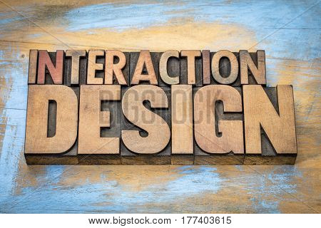 interaction design - designing interactive digital products, environments, systems, and services - word abstract in vintage letterpress wood type against grunge wooden background