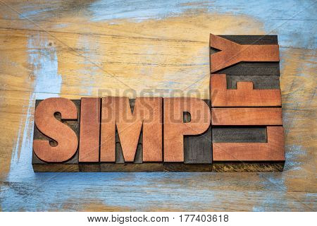 simplify word abstract in vintage letterpress wood type printing blocks stained by color inks against grunge wooden background