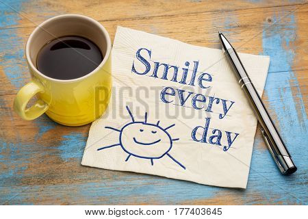 Smile every day - cheerful handwriting on a napkin with a cup of espresso coffee