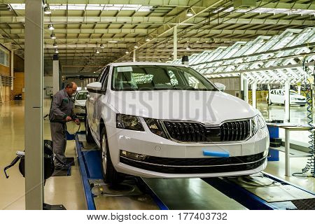 Solomonovo Ukraine - March 9 2017. The mechanic checks the pressure in the tires of the Octavia car in the workshop of the Transcarpathian plant of the Czech automaker from Škoda.