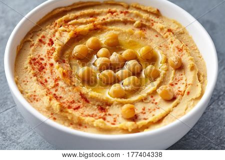 Hummus homemade traditional middle eastern dip paste close up with paprika, tahini, and olive oil, healthy diet natural vegetarian snack protein food. Traditional mediterranean appetizer on blue table