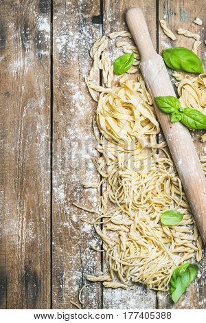 Various homemade fresh uncooked Italian pasta with flour, green basil leaves and plunger on rustic wooden background, top view, copy space, vertical composition