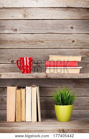 Old books on a wooden shelf, coffee cup and plant. With copy space
