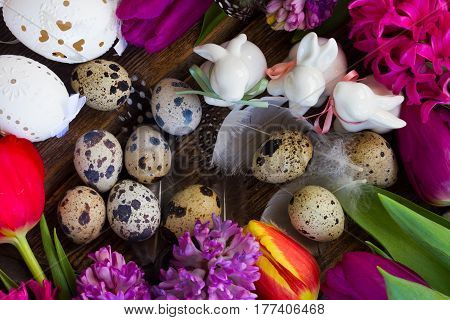 Spring fresh flowers with easter eggs and three white pocelane rabbits close up