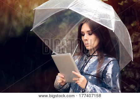 Funny Woman with Raincoat and Umbrella Holding Pc tablet