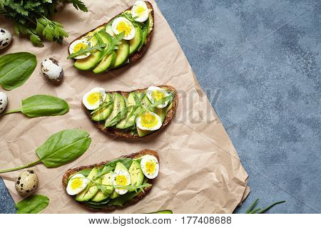 Egg and avocado sandwiches toast with guacamole, slice avocados, spinach, arugula and quail eggs on parchment paper for healthy breakfast concept. Spring food. Flat lay copy space.