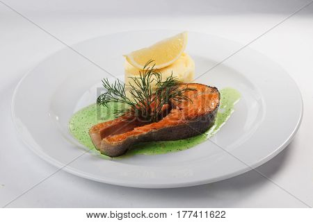 Salmon Steak with mashed potatoes on a plate isolated white background