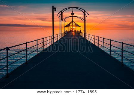People walking along Brighton Jetty at sunset
