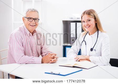 Happy patient is sitting with his doctor after the successful treatment.