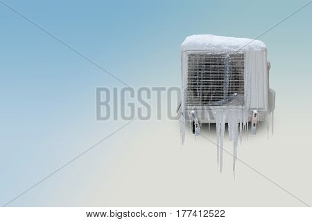 Frozen air conditioner with icicles on a blue white background. Copy space