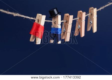 Beautiful bride and groom clothespin toys on clothesline. Abstract woman in red wedding dress and man with suit black hat. Love concept photo. Macro view, shallow depth of field, copy space blue background photo