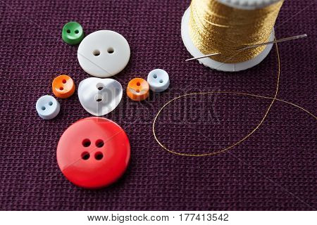 Flamenco girl conceptual design. Funny woman character made of colorful sewing buttons with needle and golden thread on violet textured textile background. macro view, shallow depth of field.