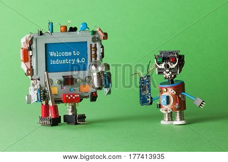 Welcome to Industry 4 robotic cyber systems, smart technology and automation process. Abstract electronic toy with circuit in hand and monitor computer robotic character, warning message on blue screen. green background macro view.