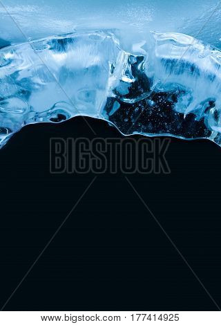 Glacial frozen ice on black. Abstract textured icicle surface macro view. Xmas decorative template background. Shallow depth of field, copy space.