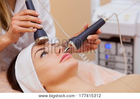 The Doctor-cosmetologist Makes The Procedure An Ultrasonic Cleaning Of The Facial Skin Of A Beautifu