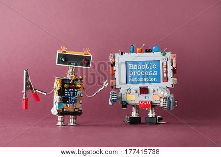 Robotic process automation industry 4.0 concept. IT specialist robot with pliers looking at colorful computer. New economic future message on blue display. Violet background, macro view