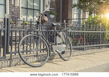 Bicycle parked at the fence. Dutch national ecological transport.