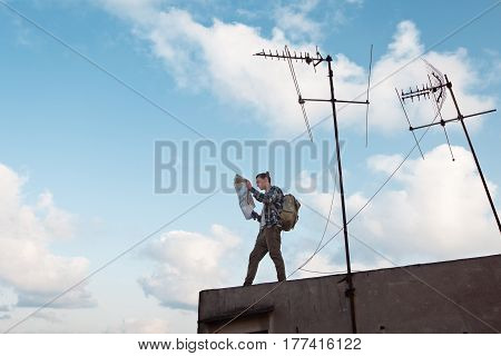 Young traveler standing at the edge of the rooftop in the city with map in hands