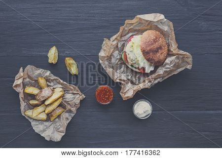 Burger and chips, restaurant dish top view. Meat cheeseburger in craft paper, potato wedges. Take away set on dark black wood background. Hamburger and spicy tomato sauce.