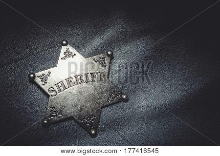 Sheriff badge on gray leather texture background. Macro shot.