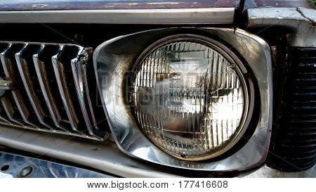 Detail of the front headlight of an old car in garage