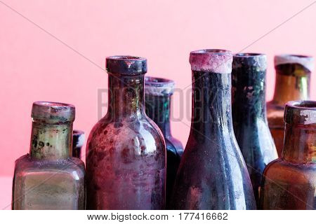 Retro design bottles macro view. Colorful dirty glass flacon set. Pink background, shallow depth of field.