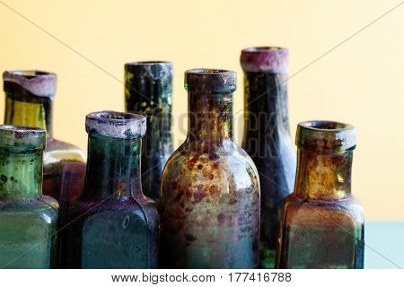 Ancient bottle macro view. Colorful transparent glass flacon set. Soft background, shallow depth of field.