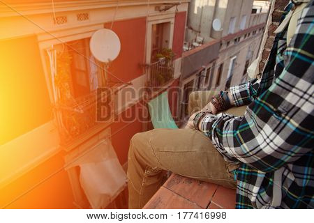 Brave man sitting on the top of the roof and relaxing