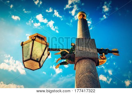 Old lamppost with small horse statue over blue sky in Saint Petersburg Russia.