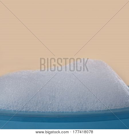 Cleaning products concept. Soapy bubbles foam on blue plastic plate and beige background. Suds and shower texture, Shallow depth of field. selective focus copy space.