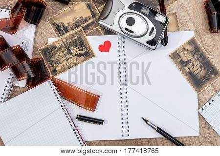 Retro camera with photo film stripe notepad pictures on desk. top view.