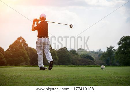 Golfers men player golf hit swing shot on course sunset.