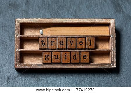Travel guide concept. Vintage box, wooden cubes phrase with old style letters, retro pencil. Gray stone textured background. Close-up, up view, soft focus