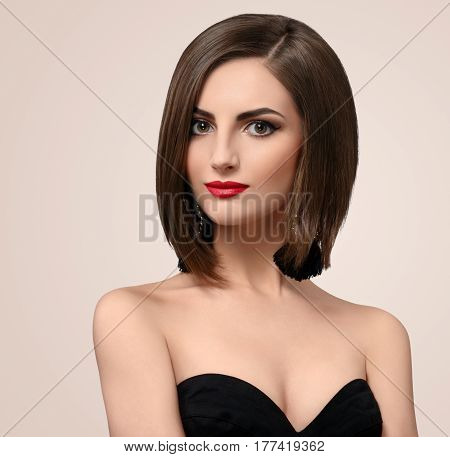 Beautiful red lipped female model wearing black dress posing sensually in studio copyspace beauty skincare makeup visage maquillage cosmetic products hairstyle concept