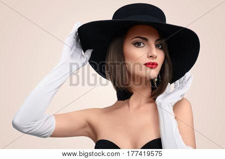Studio portrait of a beautiful classy woman wearing black dress hat and long gloves posing gracefully vintage retro classic luxury beauty makeup elegance grace femininity concept.