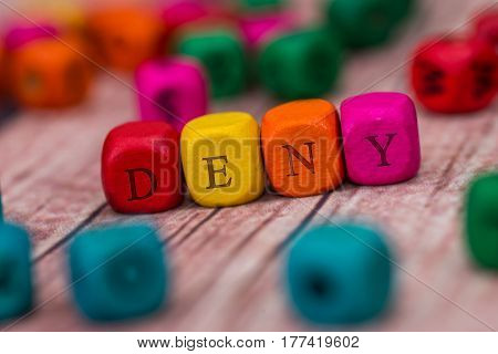 deny - word created with colored wooden cubes on desk.