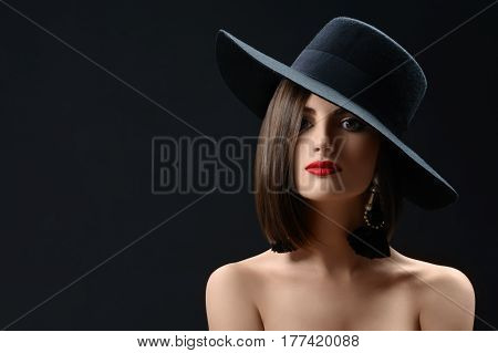 Elegant red lipped brunette fashion model posing on black background wearing a hat copyspace beauty shadow mysterious stunning hot sexy feminine confident concept