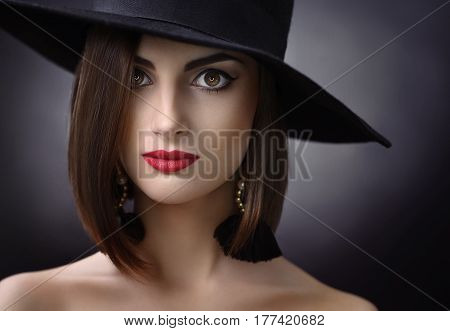 Close up studio portrait of a beautiful young brunette woman wearing evening makeup with red lips and a hat posing on dark background looking to the camera fiercely beauty mystery fashion style.