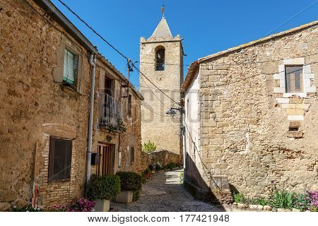 View of the medieval stone houses of the 16th century and bell tower Eglesia de Sant Esteve of 12th century. Village Sant-Esteve-de-Guialbes San Esteban de Guialbes, province Girona, Spain