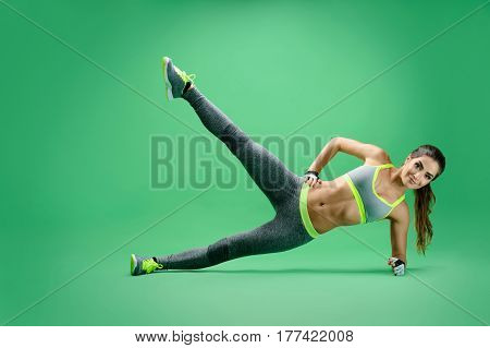 Perfecting her body. Stunning hot young fitness woman stretching out her leg while doing planking exercise at the studio gym strength stamina motivation body muscles toning shaping concept