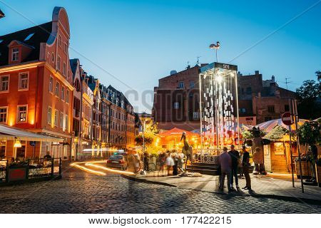 Riga, Latvia - July 1, 2016: People Walking Near Open Air Leisure Venue Recreation Center Egle In Evening Or Night Illumination In Old Town On Kalku Street.