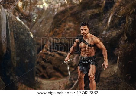 Ready to attack. Horizontal shot of a strong muscular gladiator with a sword ready to attack looking dangerous copyspace