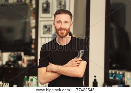 Young bearded barber at workplace