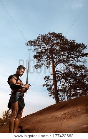 Peace in mind. Vertical portrait of a strong handsome young gladiator with muscular body holding a sword standing on a rock at the woods copyspace