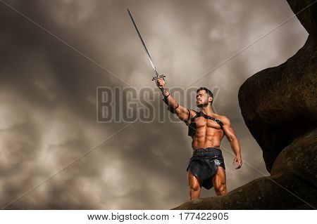 He will keep you safe. Low angle shot of a strong fierce warrior pointing his sword at the stormy sky standing on a rock copyspace