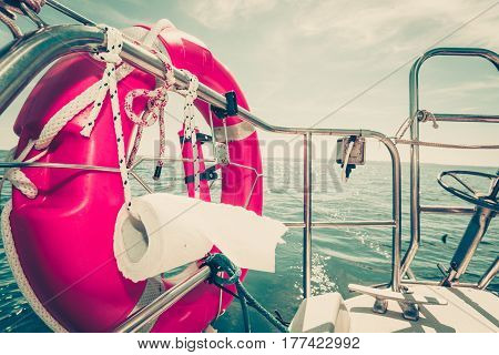 Sailing yachting equipment. Life buoy with many ropes and toilet paper on boat board