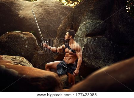He knows no defeat. Horizontal shot of a handsome muscular warrior with a sword in the woods