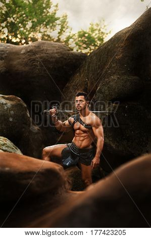 Great fighter he is. Vertical shot of a handsome stunning young man with strong muscular body looking away at the woods holding his sword standing on a rock