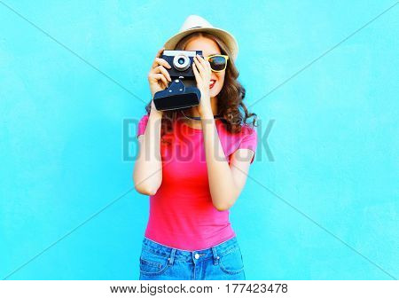 Fashion Woman Taking Picture Wearing Straw Summer Hat, Sunglasses And Vintage Camera Over Colorful B