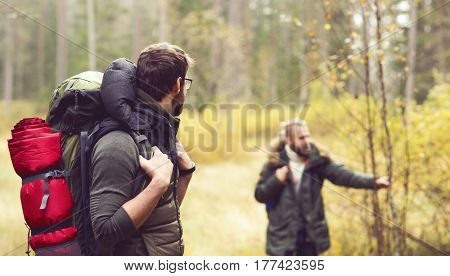 Two brutal and handsome, bearded men hiking in autumn forest. Camp, adventure, trip and fishing concept.